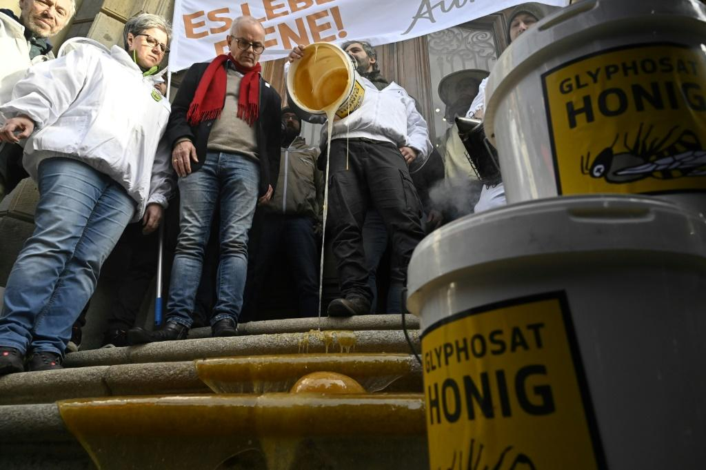 Beekeepers from the countryside outside Berlin dump buckets of honey on the steps of the Ministry for Agriculture