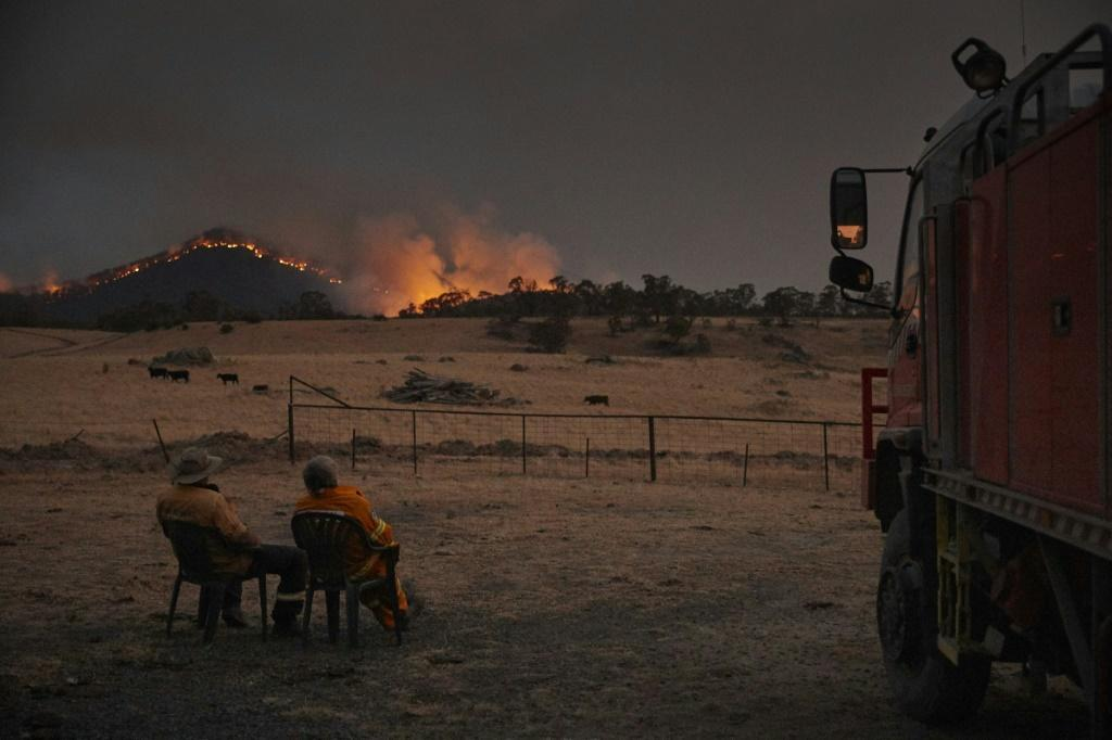 Volunteer firefighters watch as a bushfire rages on the outskirts of the town of Tumbarumba in New South Wales