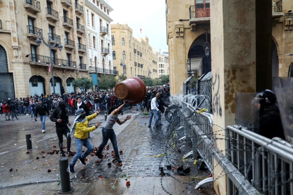 Anti-government protesters throw a large plant pot at Lebanese security forces in Beirut