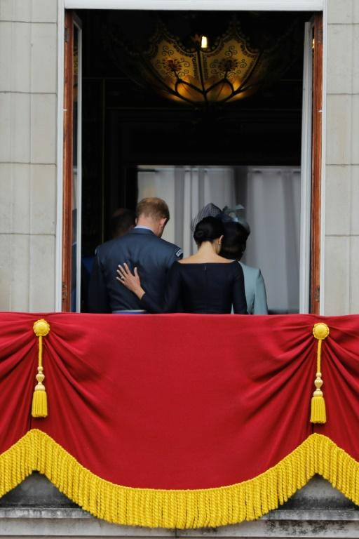 (FILES) In this file photo taken on July 10, 2018 Britain's Meghan, Duchess of Sussex (R) puts her hand on Britain's Prince Harry, Duke of Sussex's back; Britain's Prince Harry and his wife Meghan will give up their titles and stop receiving public funds