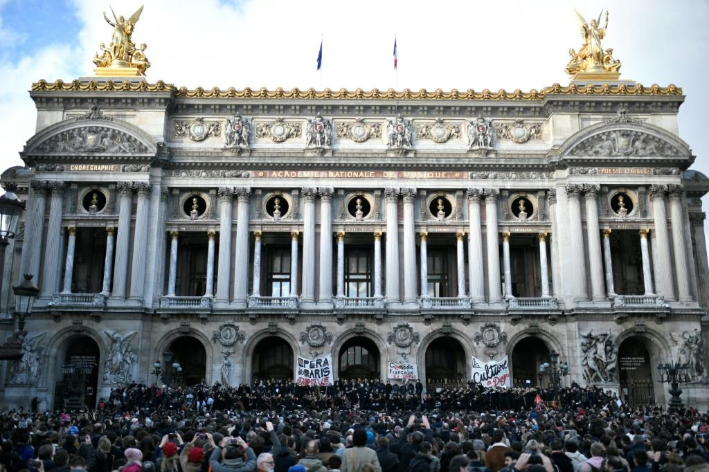 Musicians perform in front of the Palais Garnier during a demonstration of striking employees