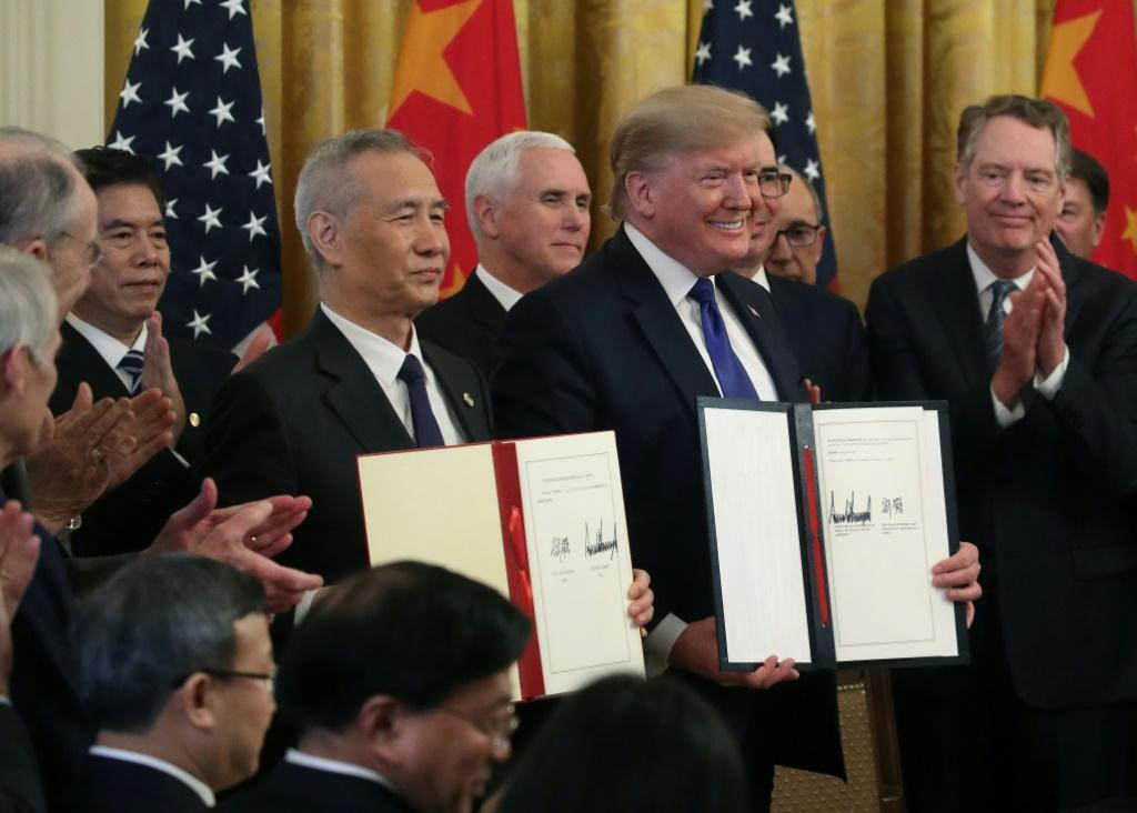 """US President Donald Trump (pictured January 15, 2020) and Chinese Vice PremierLiuHe hold up signed agreements of """"phase one"""" of a trade deal between the two countries"""