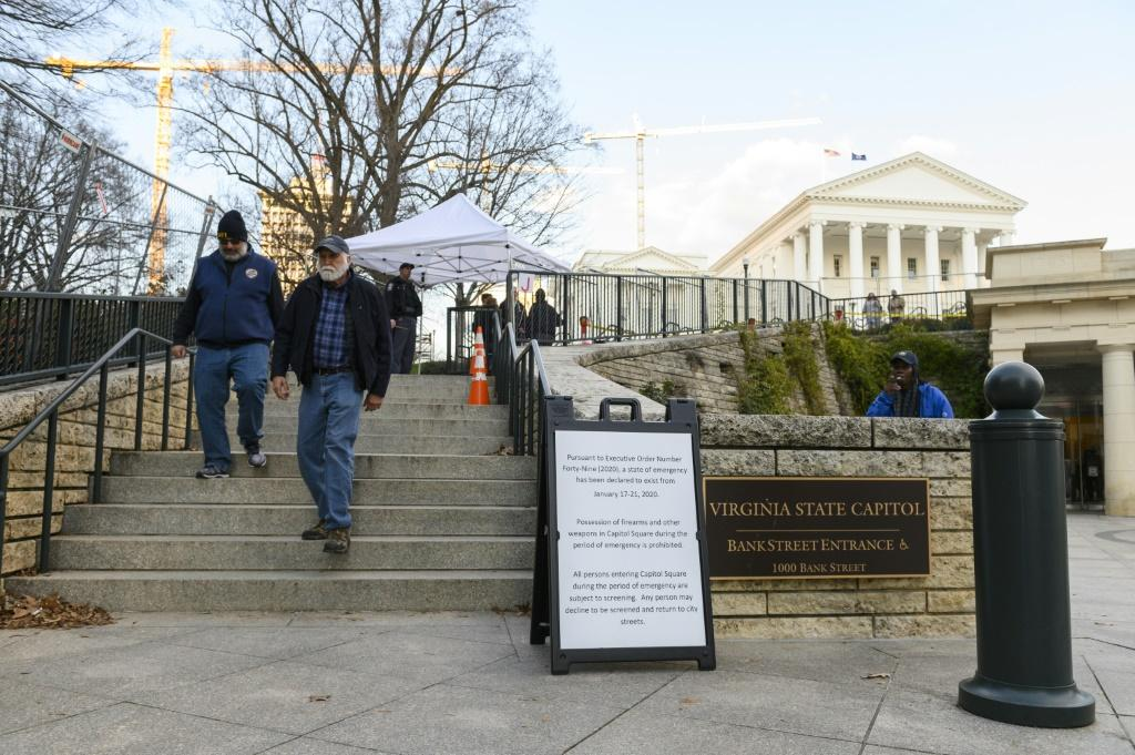 Visitors walk out of the grounds of Virginia's State Capitol in Richmond, near a sign advising that a state of emergency prohibits possession of firearms and other weapons in Capitol Square