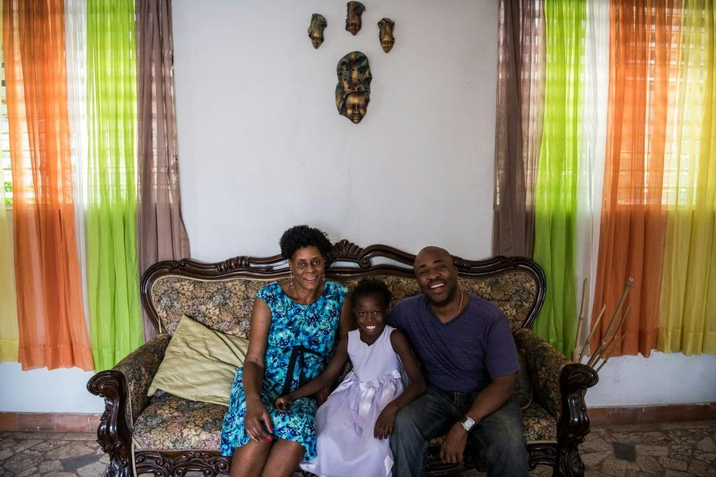 Marie Judith Blaise (L) and Joseph Hyden (R), pose with foster child Myloveda at their home, in Port-au-Prince, Haiti -- where the government of the Americas' poorest country is pushing to deinstitutionalize children