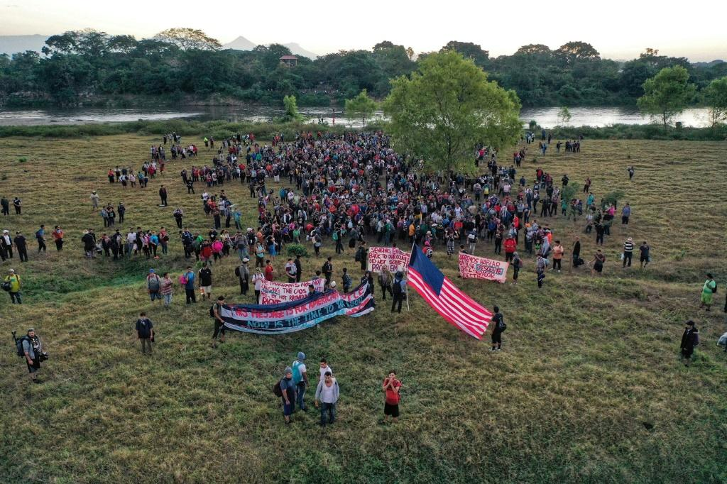 Aerial view of Central American migrants - mostly Hondurans heading in a caravan to the US - holding banners and a US flag after crossing the Suchiate River into Mexico from Guatemala