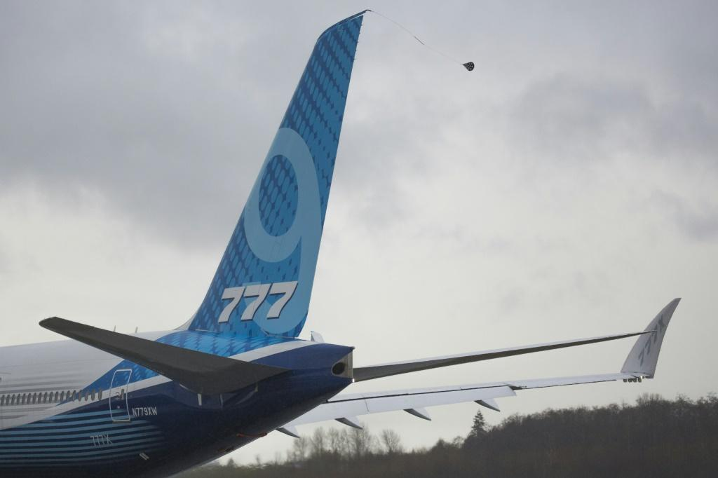 A Boeing 777X airplane taxis for the first flight, which had to be rescheduled due to weather, but the company will try again Saturday