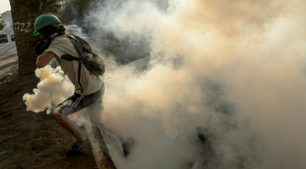 A demonstrator runs away from a tear gas canister thrown by riot police during clashes which erupted during a protest against the government of Chilean President Sebastian Pinera, in Santiago on January 24, 2020