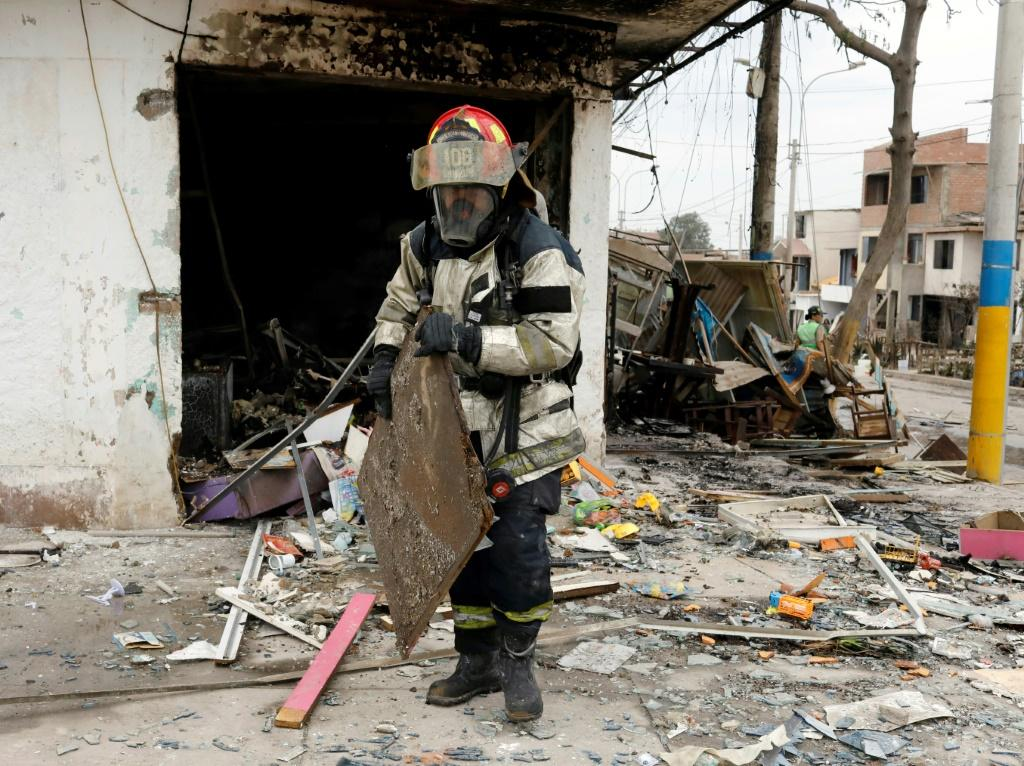 A firefighter sifts through the wreckage of a house destroyed in the blast and subsequent fire