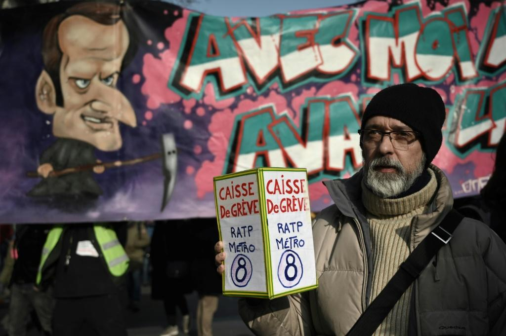 A protester holds a donation box for strikers in front of a banner portraying President Emmanuel Macron during a march against France's pension reform in Paris on Friday.