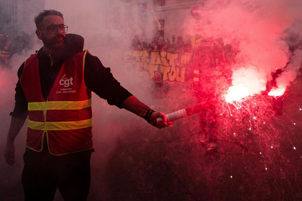 A protester wearing a gilet of the moderate CGT union brandishes a smoke bomb during Friday's demonstration in Lyon, southeast France
