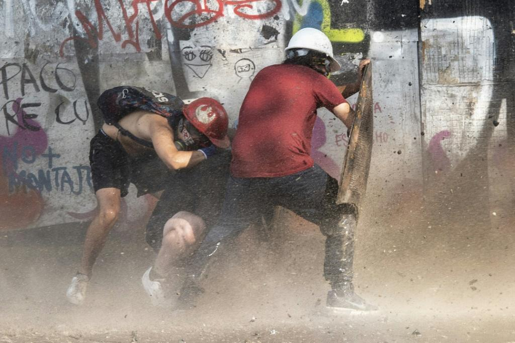 Demonstrators take cover as they clash with riot police during a protest against Chilean President Sebastian Pinera's government in Santiago, on January 17, 2020