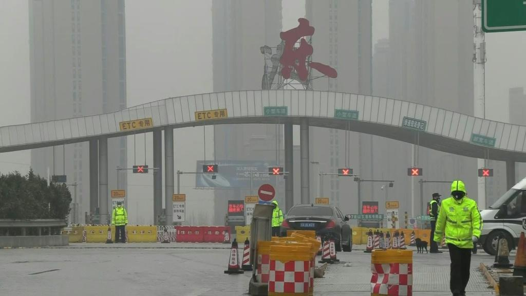 Police block roads into the Chinese city of Wuhan, which has been locked down in an unprecedented quarantine effort aimed at containing a deadly respiratory virus which has left at least 41 people dead