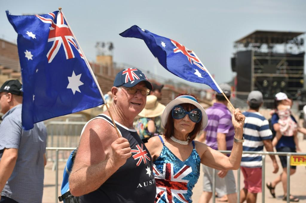 A couple wave flags to mark Australia Day in Sydney