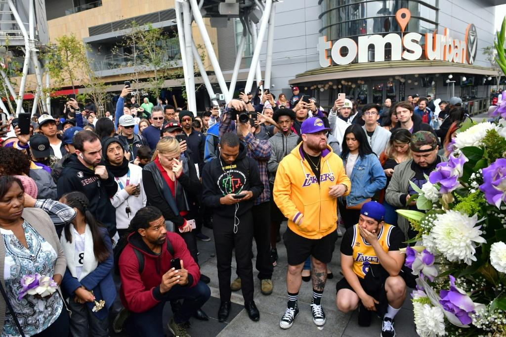 People gather around a makeshift memorial for former NBA and Los Angeles Lakers player Kobe Bryant at LA Plaza