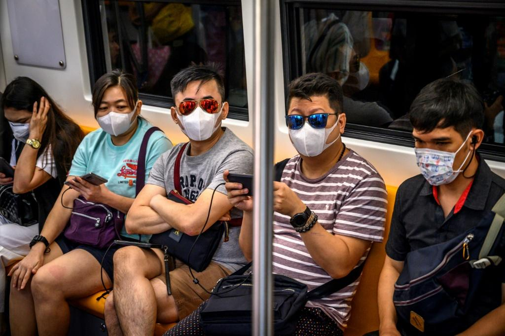 People with face masks ride a BTS Sky train in Bangkok, Thailand, which has detected eight virus cases so far, three receiving treatment in hospital and five discharged