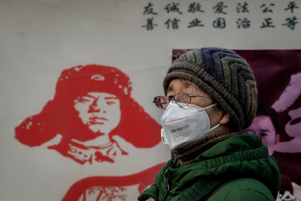 A woman in Beijing wears a protective mask to help stop the spread of the coranavirus, which has killed more than 100 people