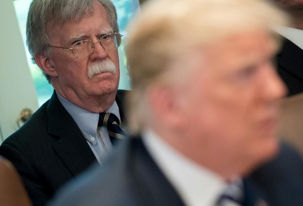 Trump's denial came after The New York Times reported that his former national security advisor John Bolton (L) says in his upcoming book that the president tied Ukraine aid to an investigation of his rivals