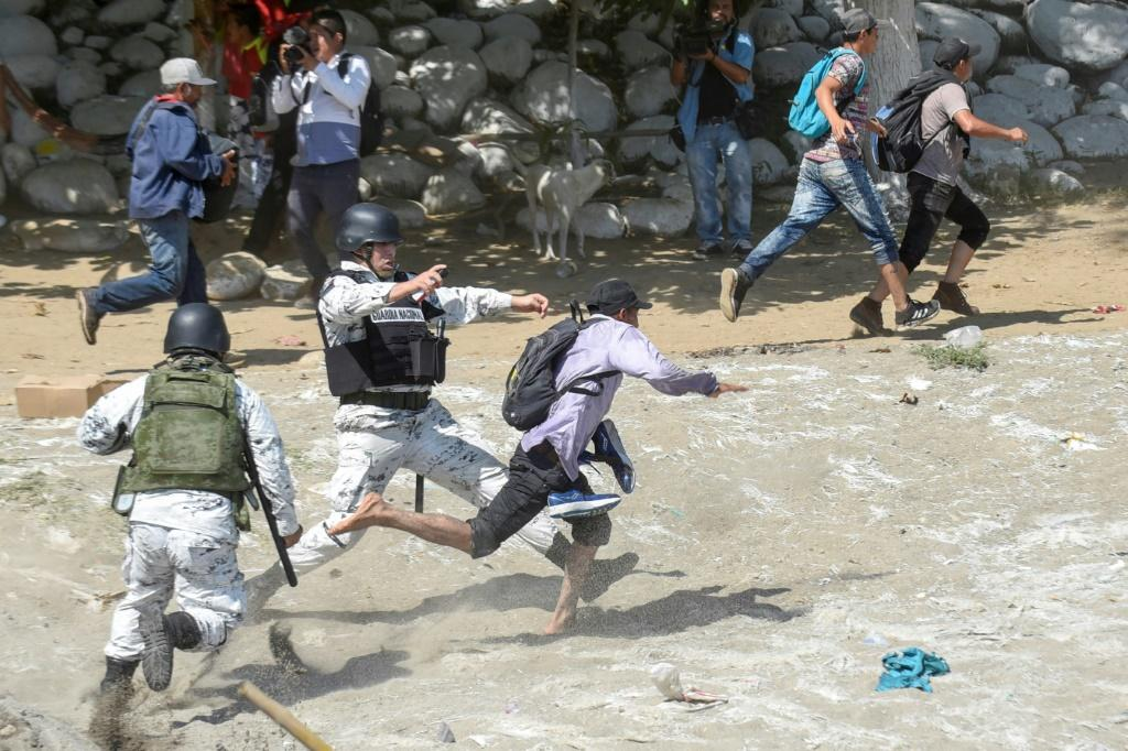 Mexican National Guards tackle migrants who crossed the Suchiate River from Guatemala on January 20, 2020