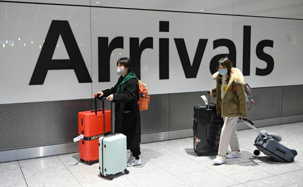 Passengers wear face masks after their flight arrived at Heathrow Airport in London