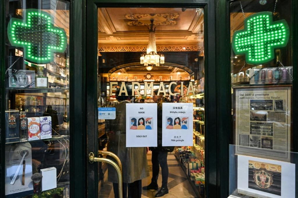 A sign in various languages, including Chinese, tells customers that masks have sold out at a pharmacy in Rome