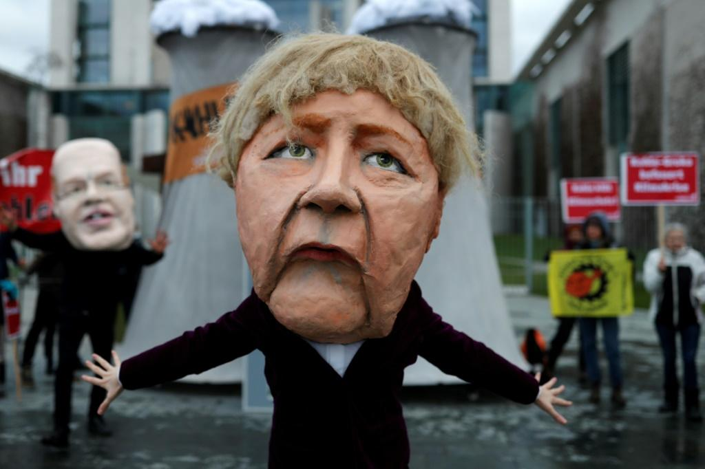 """Outside Chancellor Angela Merkel's office, marchers brandished signs reading """"Shut off the coal plants NOW"""