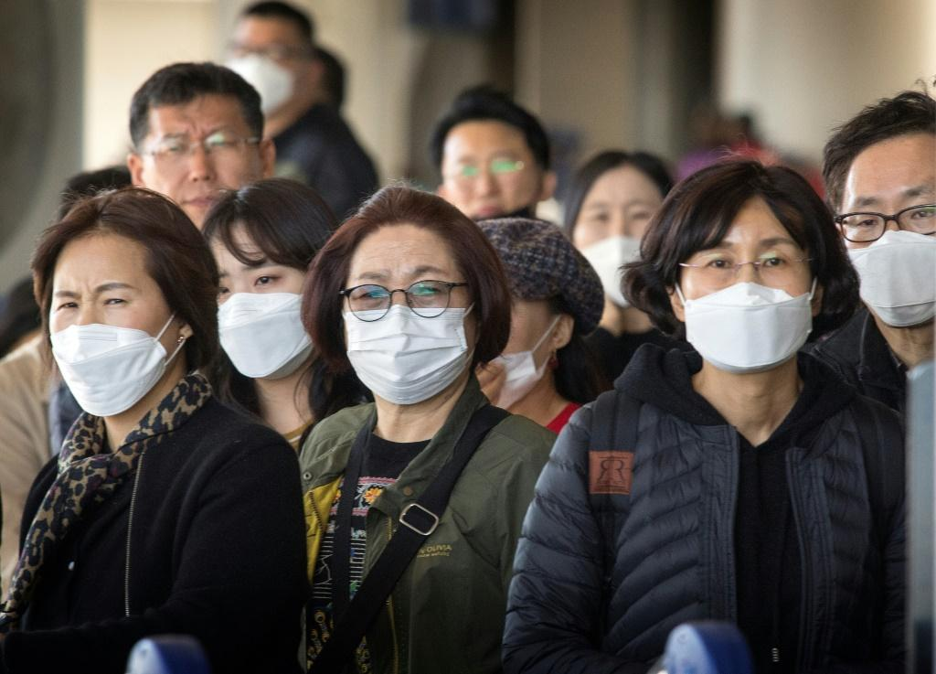 Passengers wearing face masks arrive on a flight from Asia at Los Angeles International Airport, California