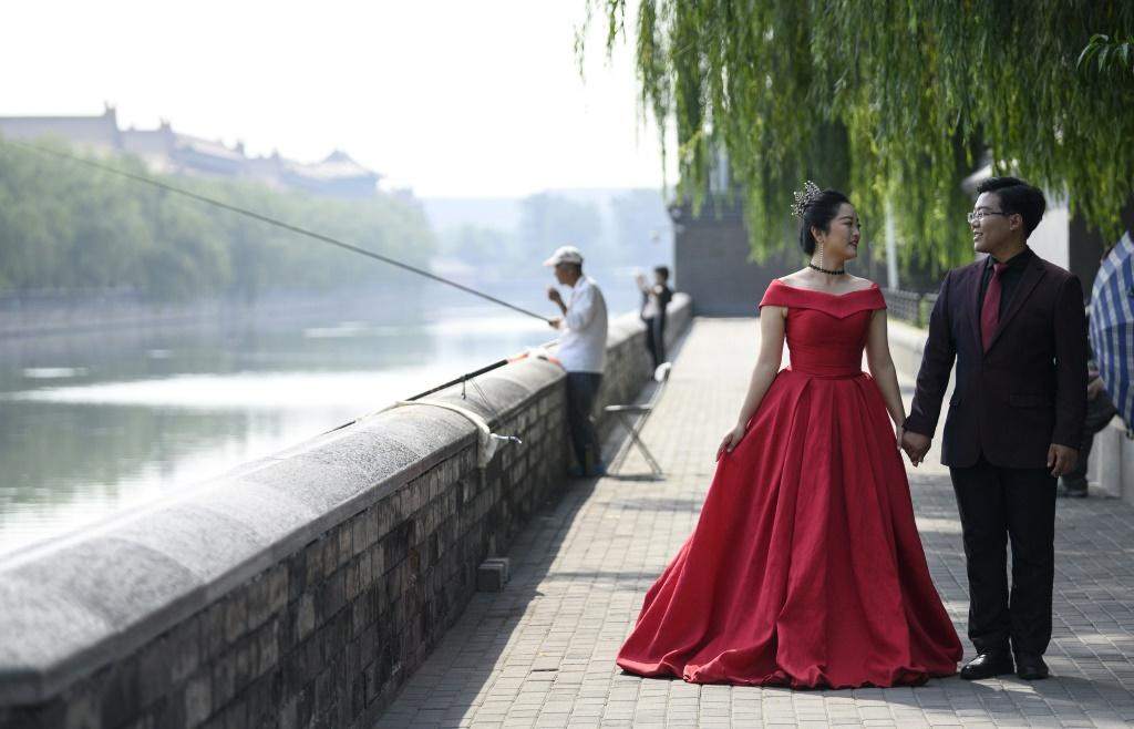 A couple pose for pre-wedding pictures at the north gate of the Palace Museum in Beijing