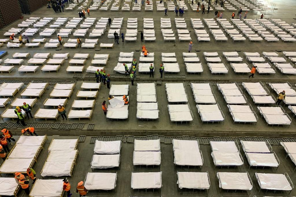 Workers set up beds at an exhibition centre converted into a hospital in Wuhan in China's central Hubei province