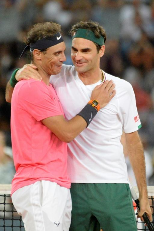 Old rivals: Nadal embraces Federer during their singles match