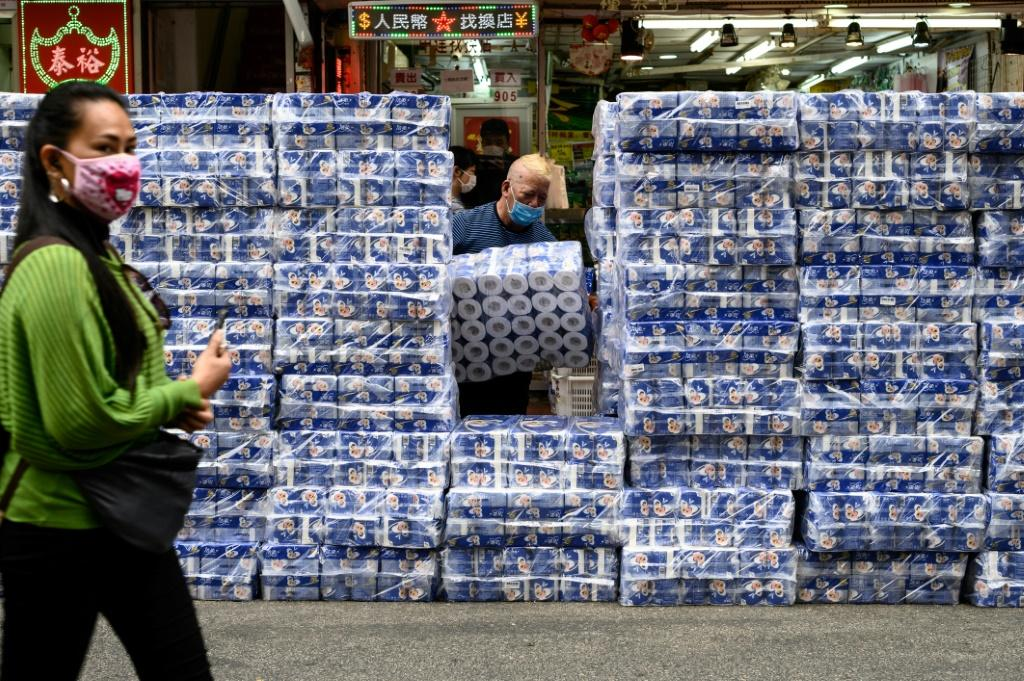 A woman wearing a protective face mask walks past stacks of toilet paper for sale in the Tsuen Wan district of Hong Kong