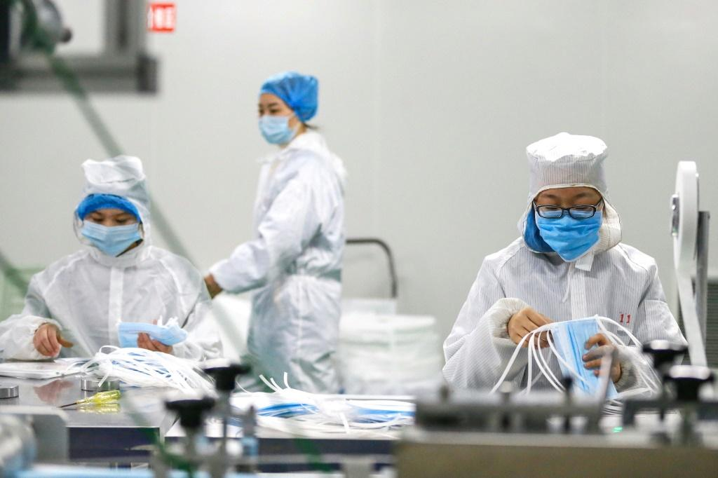 Workers produce protective masks at a factory in Qingdao, Shandong province in eastern China, during the deepening coronavirus crisis
