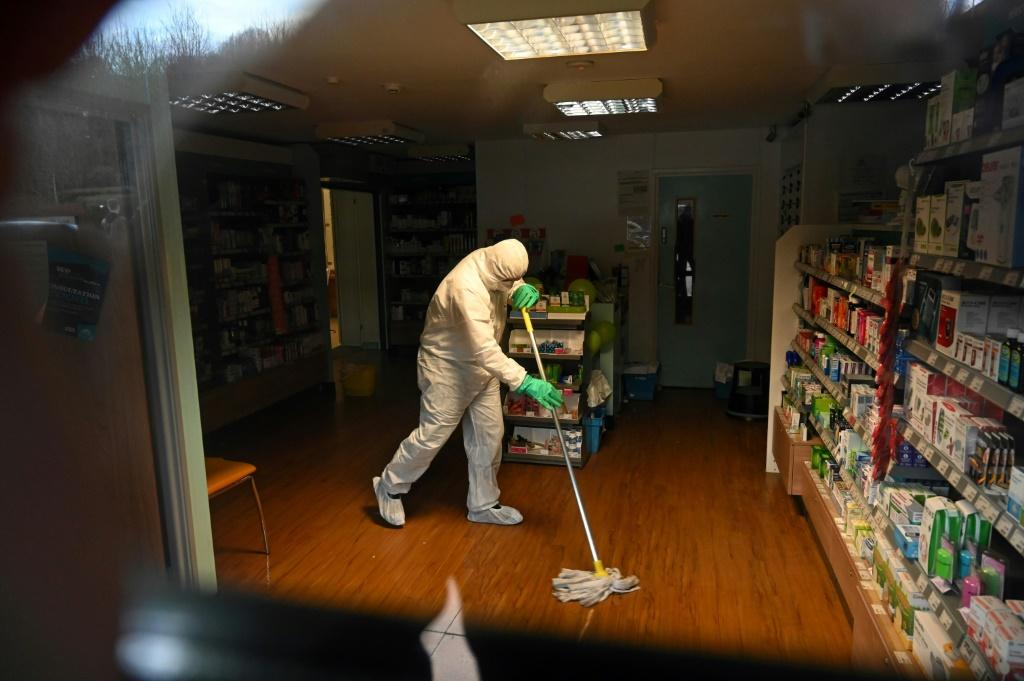 A medical worker cleans the floor of a pharmacy attached to a medical centre in Brighton, English