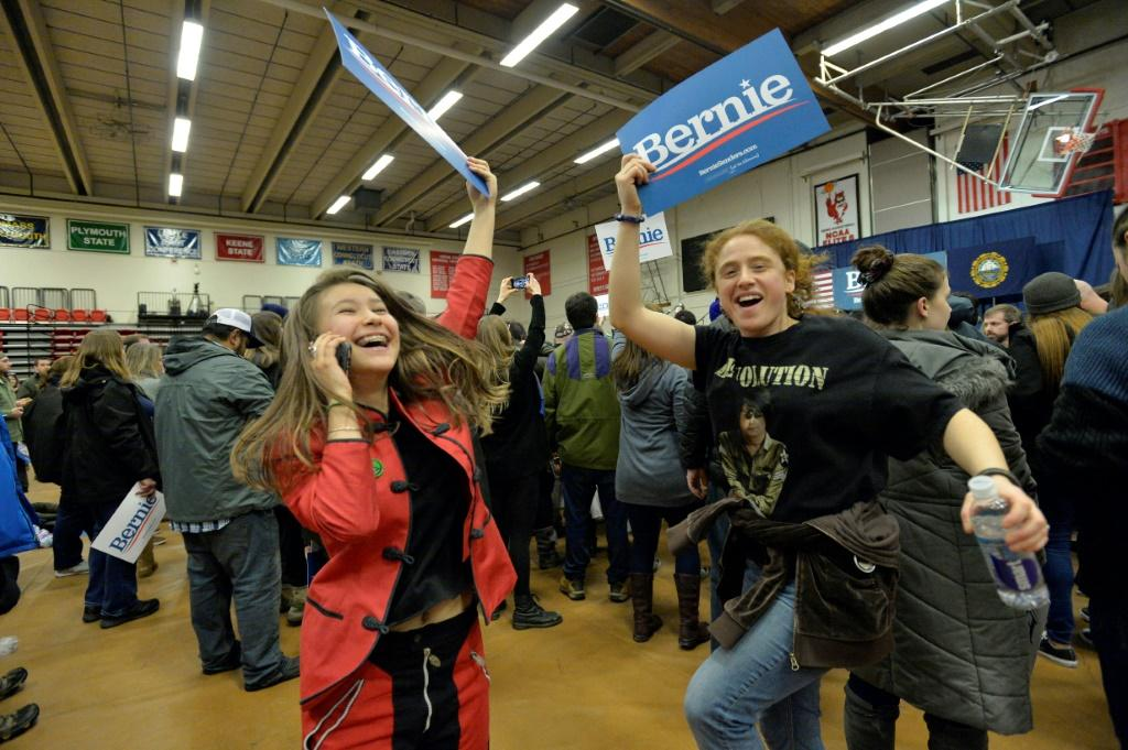 Supporters of US Presidential Candidate Senator Bernie Sanders cheer and wave campaign signs as they await his arrival at a campaign rally at Keene State College in Keene, New Hampshire on February 9, 2020.