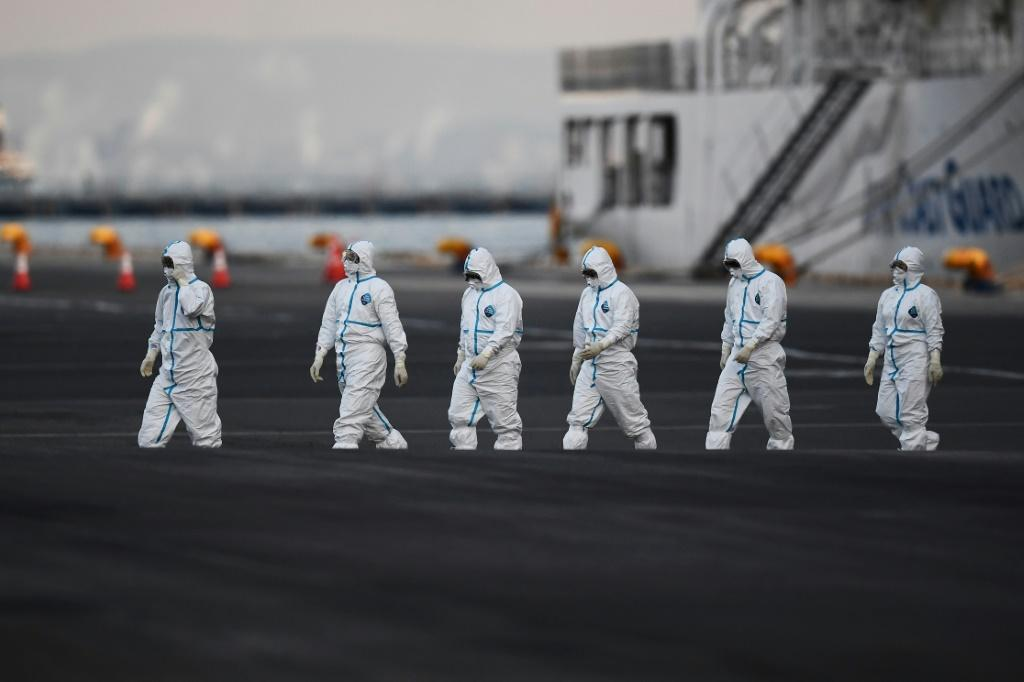 Workers in protective suits walk from the Diamond Princess cruise ship