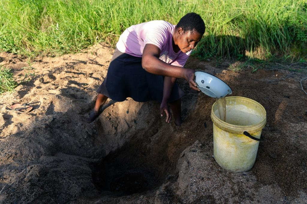 Celia Munhangu scoops through sand in search of water on the dried-up bed of the Mavhaire river in Buhera