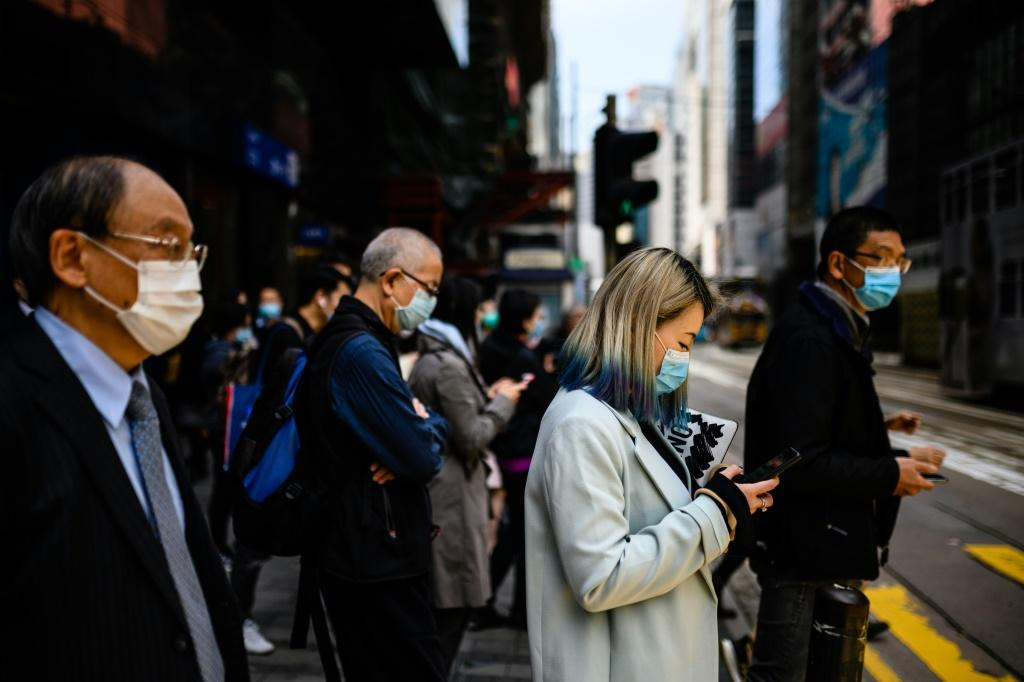 Hong Kong pedestrians wear face masks as a preventative measure against the COVID-19 coronavirus. The virus has spooked markets around the world, having killed more than 1,100 people and infected tens of thousands