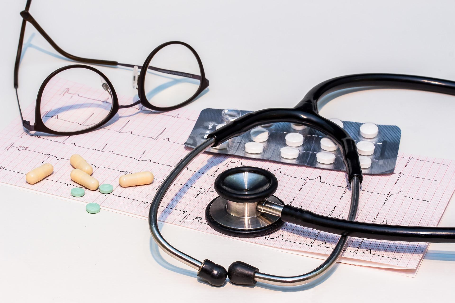 """A picture of an electrocardiogram result (""""ECG"""") result with a stethoscope and reading glasses."""