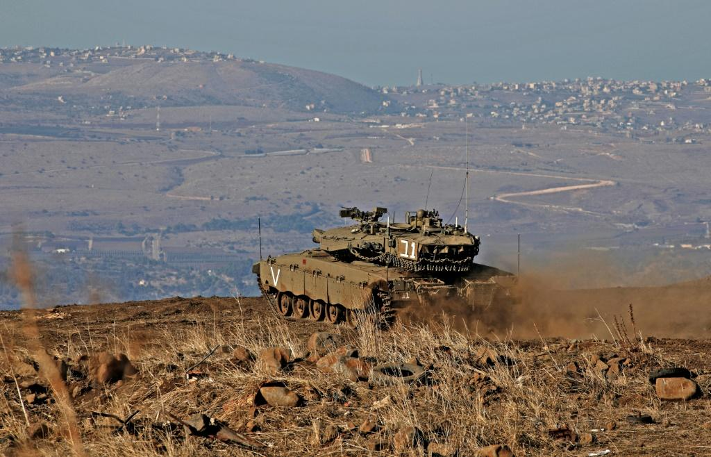 An Israeli armoured vehicle watches over Syrian government-held territory from the annexed Golan Heights
