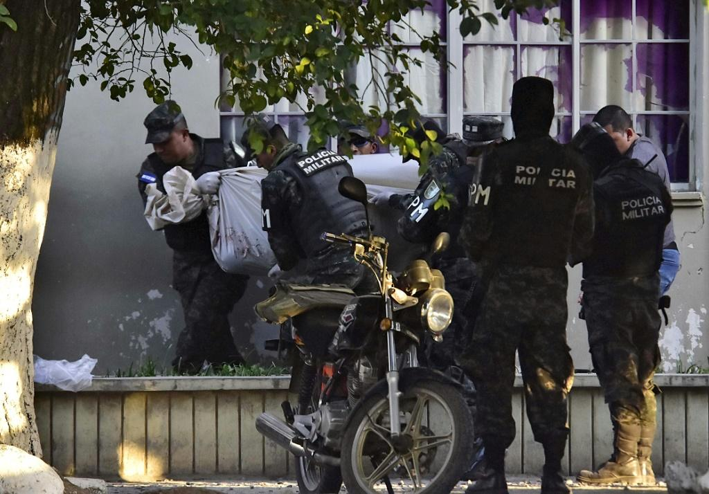 Honduran military police carry the body of a colleague after the escape of MS-13 gang leader Alexander Mendoza on February 13, 2020