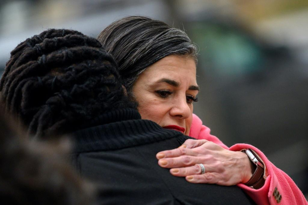 Parisa Dehghani-Tafti comforts the daughter of a murder victim, who she meets outside the courthouse in Arlington, Virginia