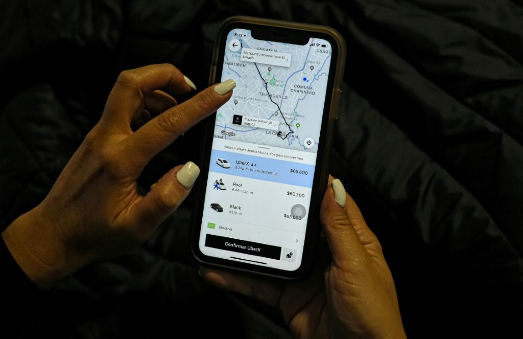 A woman checks the Uber transport application on her mobile phone after authorities ordered its suspension in Colombia, in Bogota on December 20, 2019