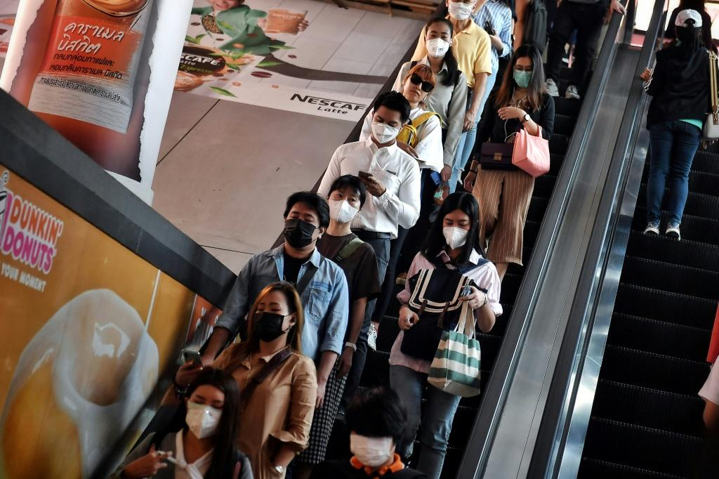 People wearing protective face masks ride down an escaltor during the morning commute in Bangkok