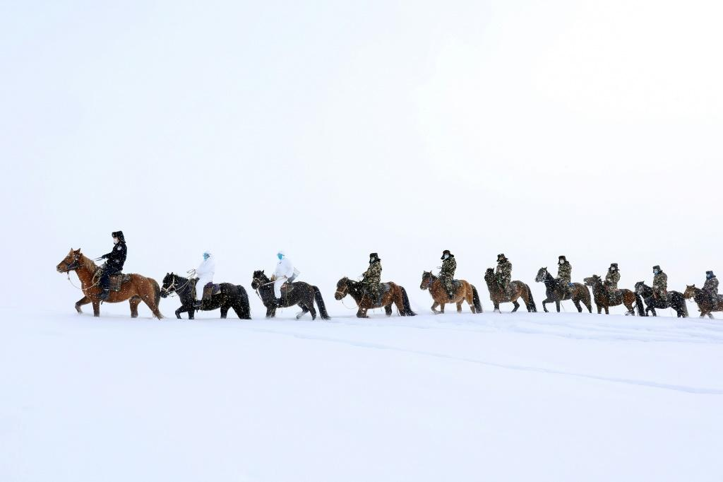 Police officers wearing protective face masks ride horses through the snow to visit residents of remote Altay in China's Xinjiang region, and promote the awareness of the Coronavirus