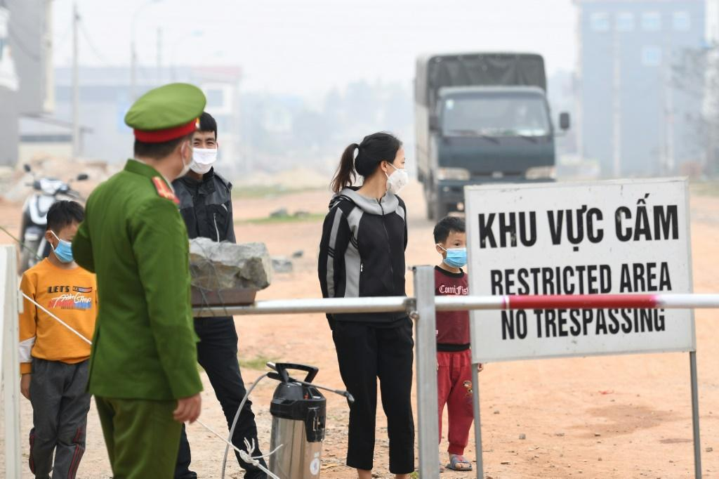 Residents stand behind a quarantine checkpoint in the Son Loi commune in Vinh Phuc province in Vietnam