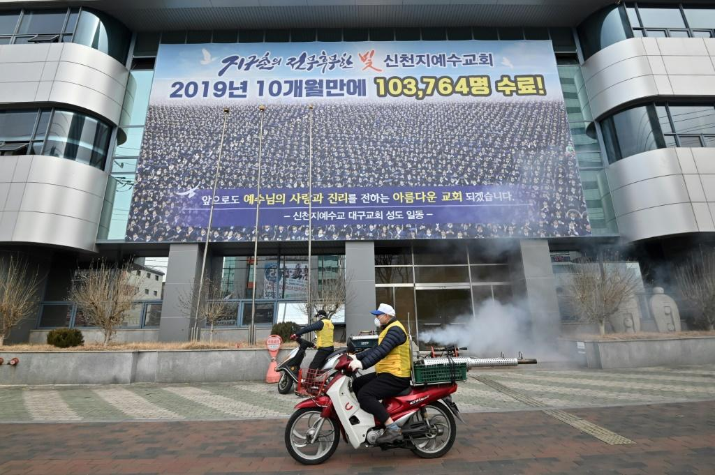 Workers spray disinfectant outside the Shincheonji church in the South Korean city of Daegu after members fell ill with the novel coronavirus