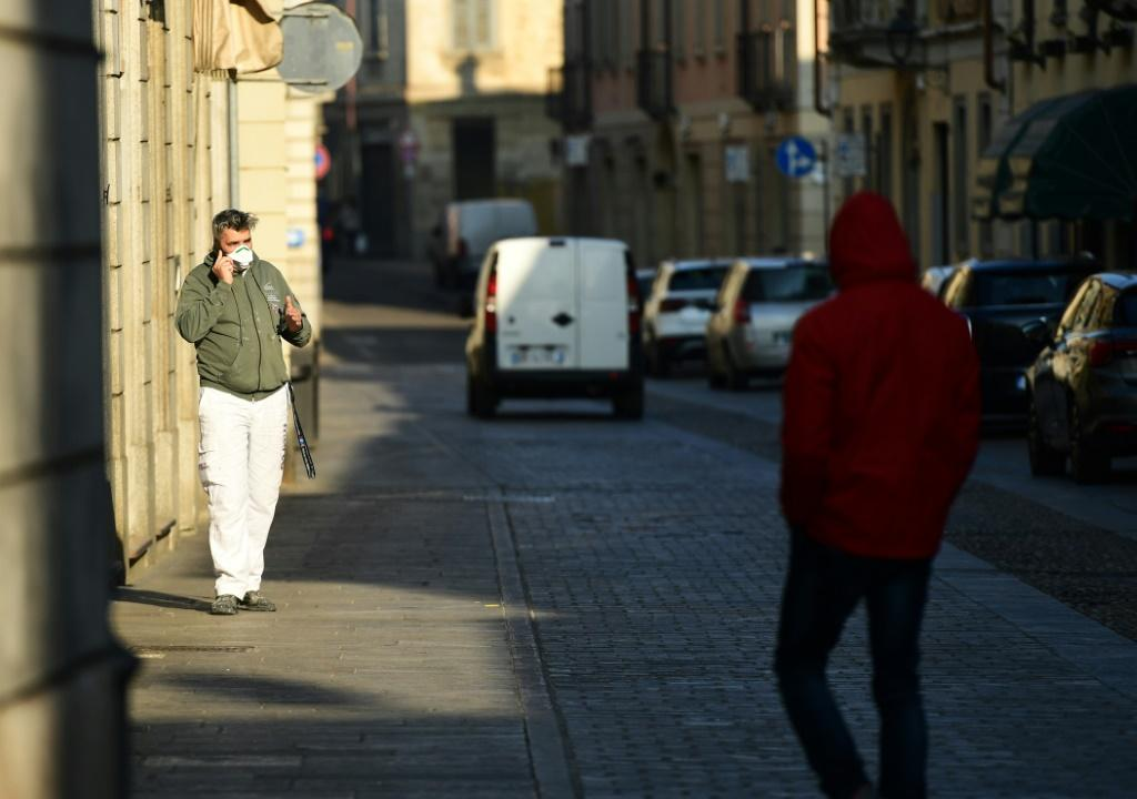 A resident wearing a protective mask in a street of Codogno, southeast of Milan. An Italian man became the first European to die after being infected with the coronavirus just hours after 10 other towns were locked down following a flurry of new cases.