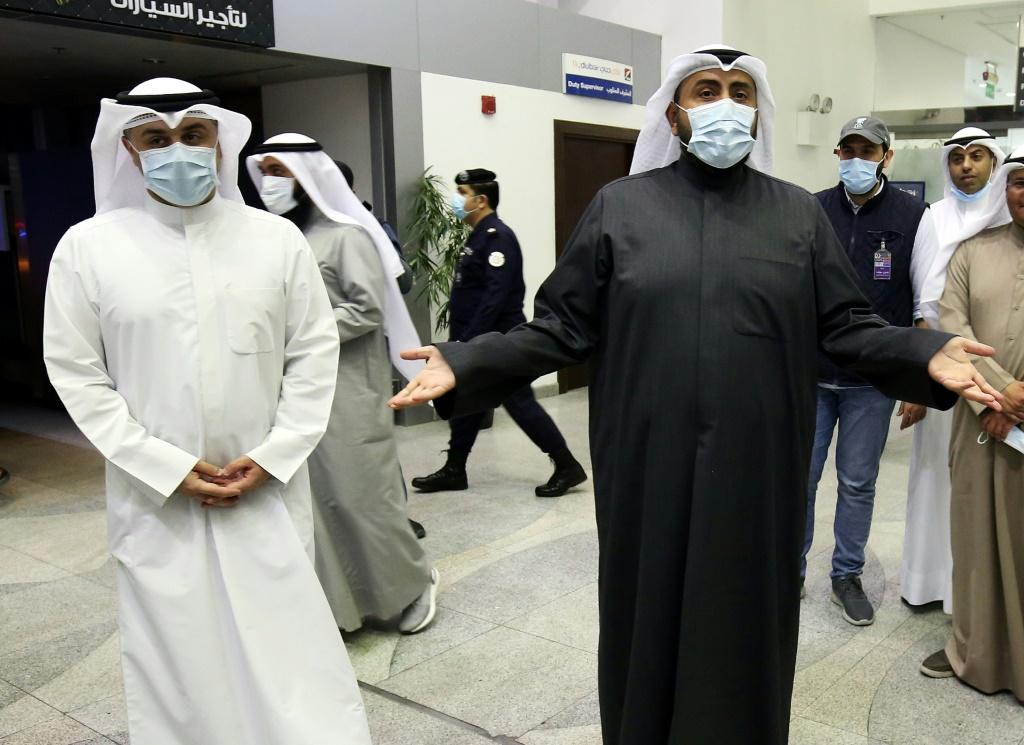 Kuwaiti health minister Sheikh Basel al-Sabah (R) speaks to the press at Sheikh Saad Airport on Sunday, as Kuwaitis returning from Iran wait before being taken to hospital to be tested for coronavirus
