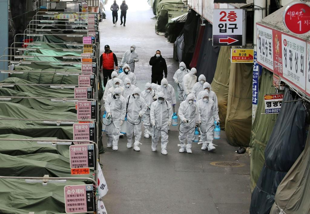 Market workers wearing protective gear spray disinfectant at a market in the southeastern city of Daegu