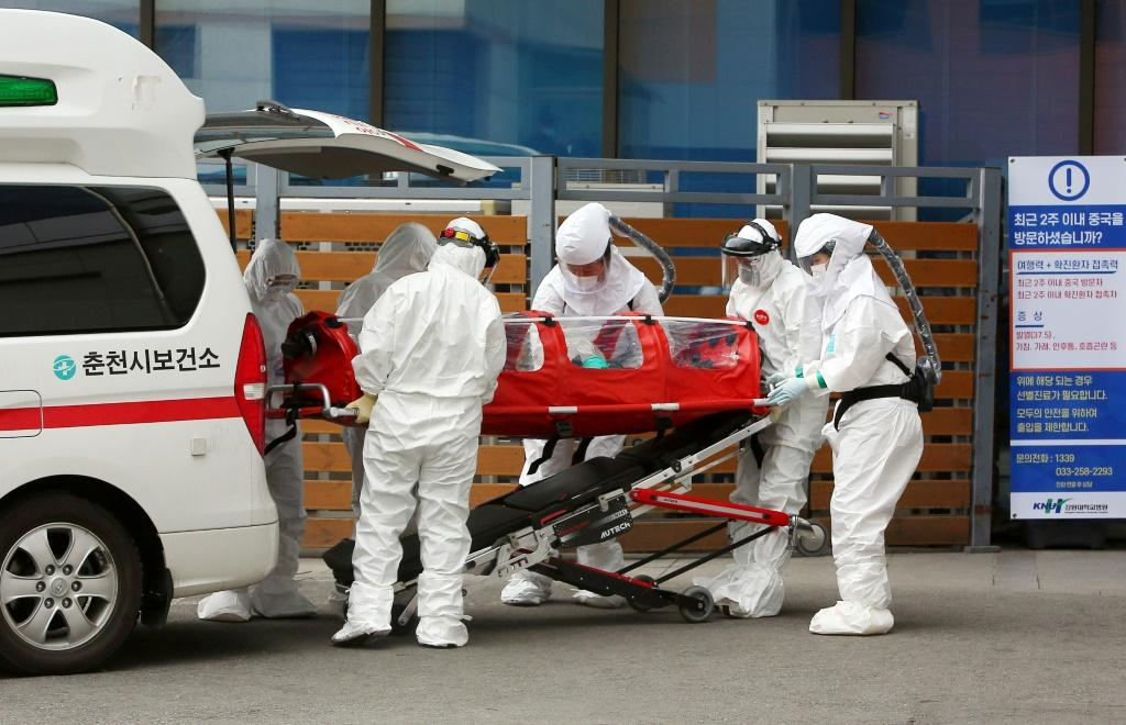 Medical workers wearing protective gear carry a patient infected with coronavirus to hospital in Chuncheon