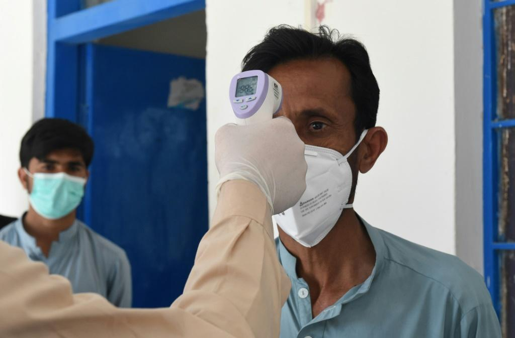 A doctor checks the body temperature of a man returning from Iran at a quarantine zone to test for the COVID-19 coronavirus in the Pakistan-Iran border town of Taftan on February 25, 2020